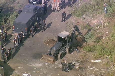 Policias usam escavadeiras para procurar covas