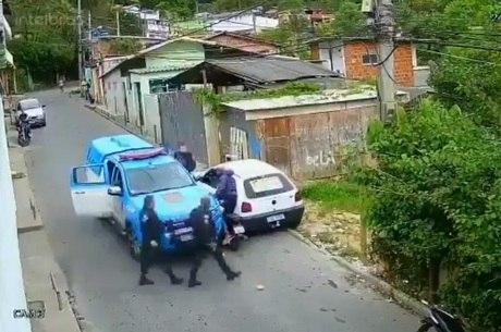 Policiais descem da viatura para abordar motociclista