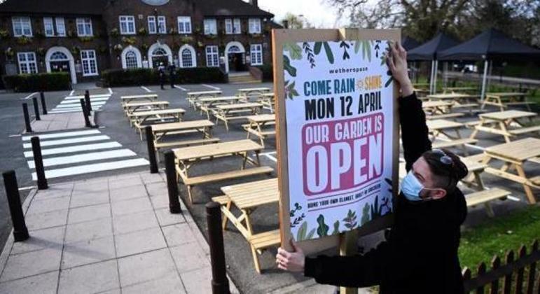 """Empreendedor segura cartaz que diz: """"Nosso jardim está aberto"""""""