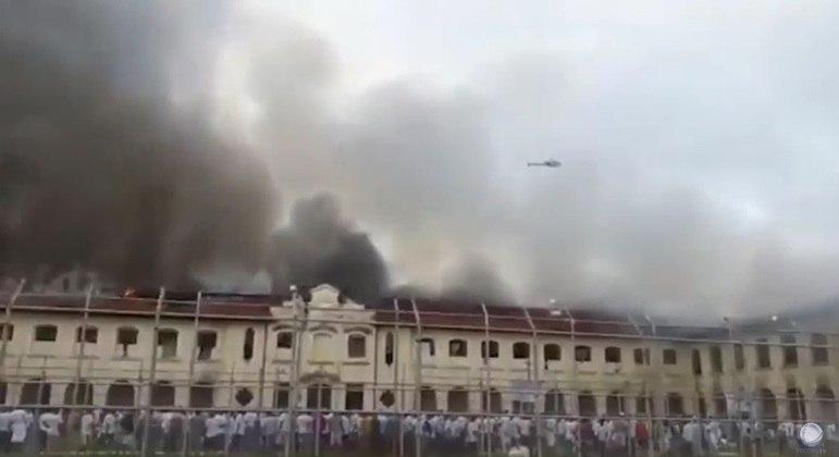 Detentos em frente ao presídio após atearem fogo nos pavilhões