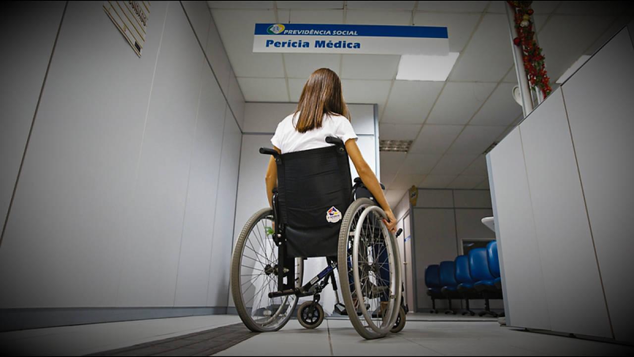 Imagem de uma mulher cadeirante em uma agência do INSS