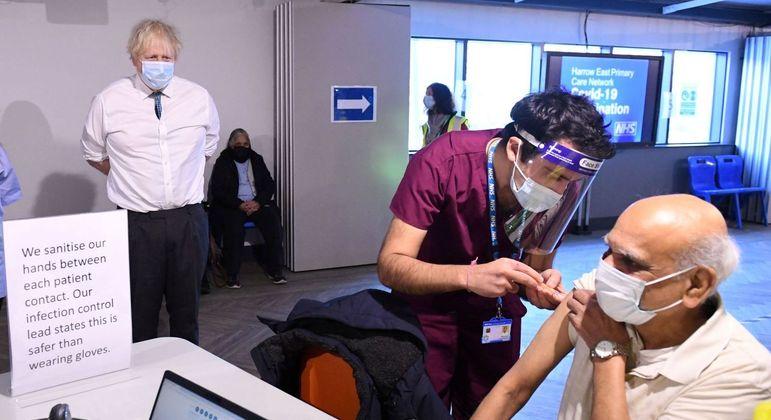 Boris Johnson observa homem recebendo dose da vacina Oxford/AstraZeneca, em Londres