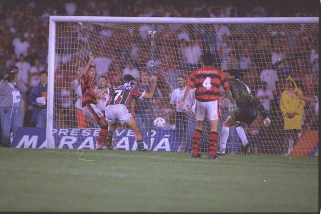 """Um dos jogos mais épicos da história do Fluminense foi a decisão de 1995. Tecnicamente não foi uma final, já que era a última rodada de um octagonal aquele 25 de junho, finalizando os 169 jogos disputados naquela edição do Estadual. Com mais de 100 mil pessoas no Maracanã e muita chuva no primeiro tempo, o Fla tinha a vantagem do empate. Renato Gaúcho abriu o placar para o Flu aos 30 minutos do 1º tempo, e Leonardo ampliou aos 42. O Flamengo reagiu na segunda etapa e Romário fez seu primeiro gol contra o Tricolor aos 26, e seis minutos depois Fabinho igualou o placar. Na súmula, a """"barrigada"""" de Renato, aos 41, foi anotada para Ailton Ferraz, atual treinador do Sub-23 do Flu"""