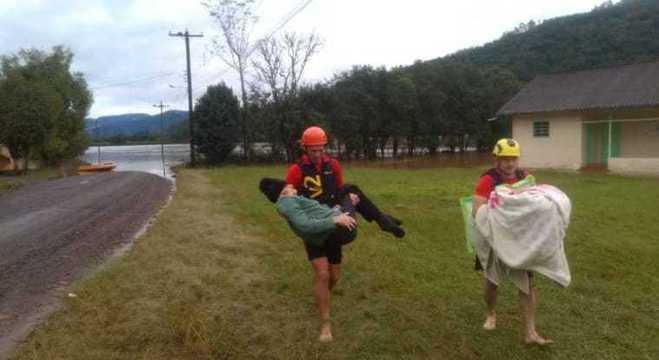 Bombeiros carregando casal pela região do rio Taquari
