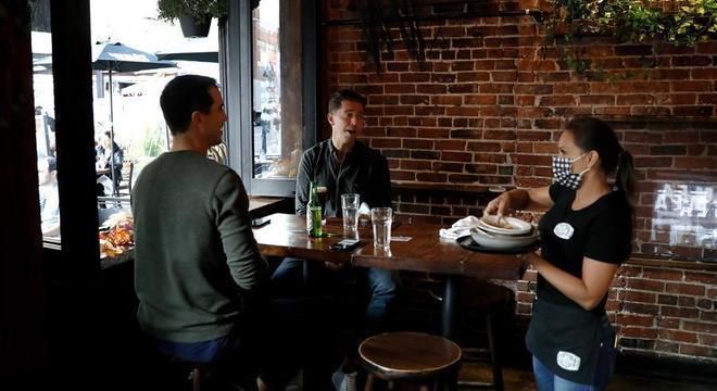Garçonete usa máscara enquanto atende clientes em restaurante de NY