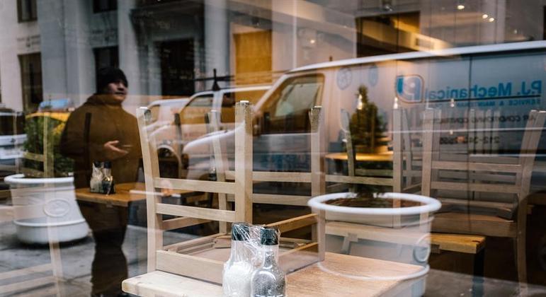 Já sem máscara, homem passa em frente a restaurante fechado em Nova York