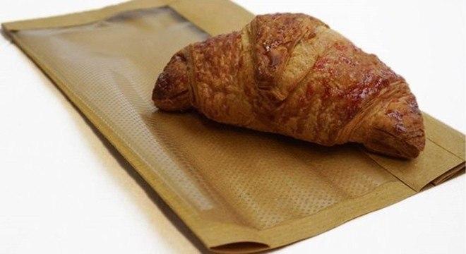 A alternativa para plástico criada por Hughes pode substituir sacos de padaria; na foto, o invento de Hughes por cima de um saco de padaria