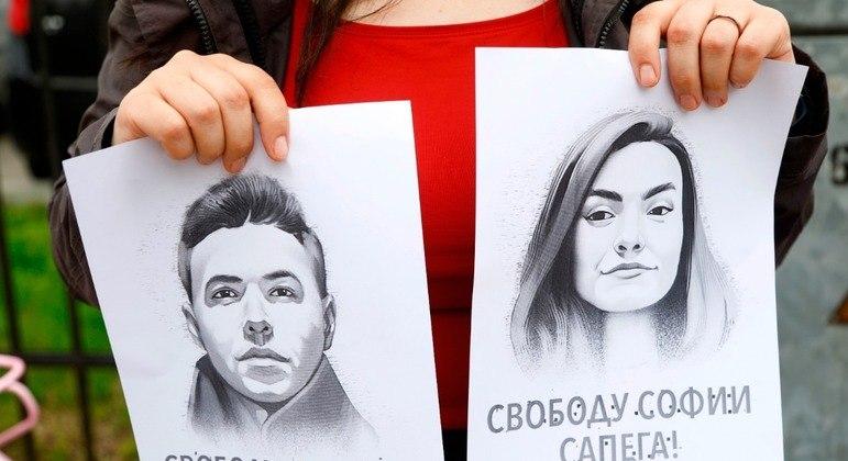 Em protesto nesta terça-feira (25), uma mulher segura os retratos do jornalista e sua namorada