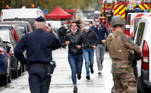 People walk towards security forces at the scene of an incident near the former offices of French magazine Charlie Hebdo, in Paris, France September 25, 2020. REUTERS/Charles Platiau