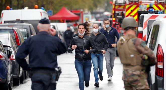 Pessoas correm nas proximidades da redação da revista Charlie Hebdo após ataque