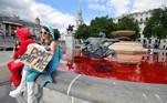 Animal rights activists sit at a fountain whose water was turned red after protesters poured coloured dye into the clear water, on Trafalgar Square in London, Britain, July 11, 2020. REUTERS/Toby Melville