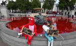 Animal rights activists hold signs as they sit at a fountain whose water was turned red after protesters poured coloured dye into the clear water, on Trafalgar Square in London, Britain, July 11, 2020. REUTERS/Toby Melville