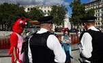 Police officers speak with animal rights and environmental activists next to a fountain whose water was turned red after protesters poured coloured dye into the clear water, on Trafalgar Square in London, Britain, July 11, 2020. REUTERS/Toby Melville
