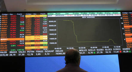 FILE PHOTO: A man stands in front of an electronic display at B3 Brazilian Stock Exchange in Sao Paulo, Brazil, March 16, 2020 REUTERS/Rahel Patrasso/File Photo