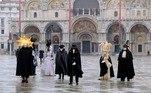 Com máscaras e fantasias típicas do Carnaval de Veneza, foliões passeiam pela cidade italiana