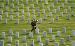 A member of the armed forces takes part in the Flags-In ceremony, where over 1,000 service members place flags in front of more than 260,000 headstones in Arlington National Cemetery in Arlington, Virginia, U.S., May 27, 2021. REUTERS/Kevin Lamarque TPX IMAGES OF THE DAY