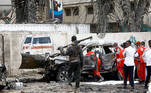 A police officer keeps watch as Red Crescent workers remove the body of a victim at the scene of a suicide car bomb explosion near the president's residence, in Mogadishu, Somalia, September 25, 2021. REUTERS/Feisal Omar TPX IMAGES OF THE DAY