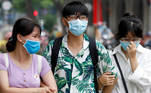 People wear protective masks as they walk down a street in Hanoi, Vietnam July 27, 2020. REUTERS/Kham