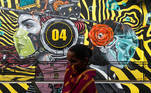 A woman walks past a graffiti of people wearing protective masks amidst the spread of the coronavirus disease (COVID-19), on the outskirts of Mumbai, India, December 9, 2020. REUTERS/Francis Mascarenhas