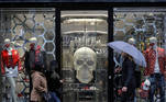 People wearing protective masks walk past a store, amid the outbreak of the coronavirus disease (COVID-19), in London, Britain October 13, 2020. REUTERS/Simon Dawson