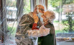 Resident kisses a relative through a plastic sheet installed in a special 'hug room' organised to keep both parties safe from novel coronavirus infection, at a care home in Castelfranco Veneto, Italy, in this handout photo released on November 11, 2020. Centro residenziale per anziani Domenico Sartor/Handout via REUTERS ATTENTION EDITORS THIS IMAGE HAS BEEN SUPPLIED BY A THIRD PARTY. TPX IMAGES OF THE DAY