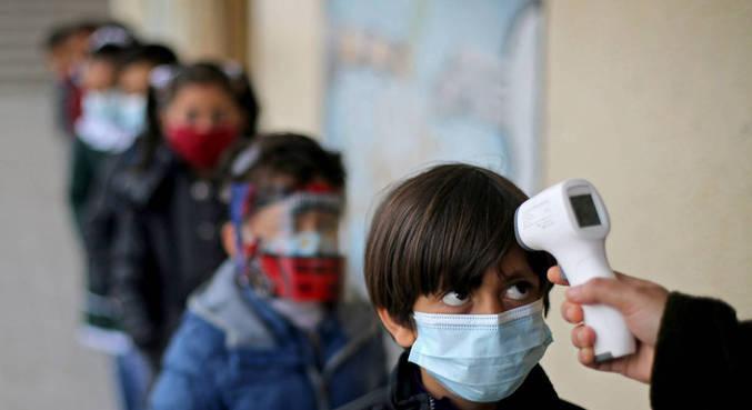Criança tem temperatura checada no volta às aulas na Palestina