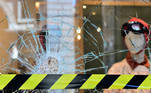 A safety tape is seen in front of a smashed window, after last night's demonstration when people protested against the new restrictions introduced by the government to curb the coronavirus disease (COVID-19) infections, in Turin, Italy, October 27, 2020. REUTERS/Massimo Pinca