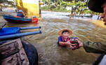 A boy gets food donation from a volunteer at a flooded area in Quang Binh province, Vietnam October 22, 2020. Picture taken October 22, 2020. Thanh Dat/VNA via REUTERS. Best quality available. THIS IMAGE HAS BEEN SUPPLIED BY A THIRD PARTY. NO RESALES NO ARCHIVES. VIETNAM OUT. NO COMMERCIAL OR EDITORIAL SALES IN VIETNAM TPX IMAGES OF THE DAY