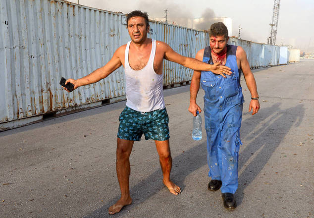 Dois homens correm, tentando se afastar do local da explosão
