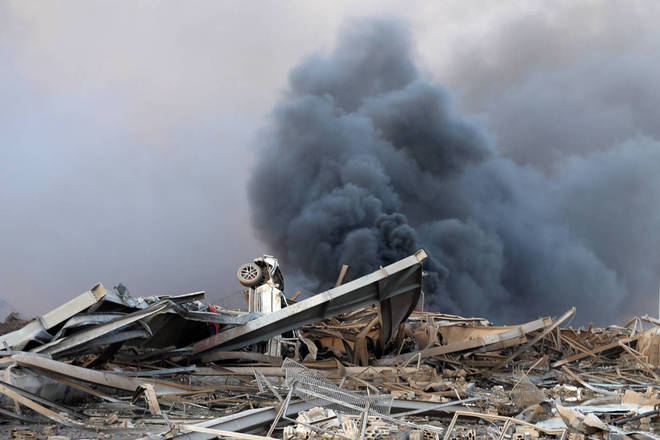 Um carro sob escombros dos prédios destruídos do porto após a explosão