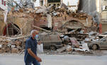 A man walks past damaged building and vehicles near the site of Tuesday's blast in Beirut's port area, Lebanon August 5, 2020. REUTERS/Aziz Taher