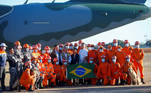 Brazil's President Jair Bolsonaro poses for a photo with firefighters before they depart for a rescue mission in Haiti, at Brasilia Air Base in Brasilia, Brazil August 22, 2021. REUTERS/Adriano Machado