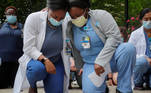 Nurses Sasha Dubois and Farah Fevrin kneel for the 8 minutes and 46 seconds of silence during a vigil at Brigham and Women's Hospital, where many coronavirus disease (COVID-19) patients have been treated, against the death in Minneapolis police custody of George Floyd, in Boston, Massachusetts, U.S., June 5, 2020. REUTERS/Brian Snyder