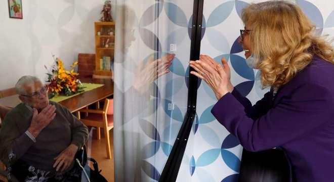 Mulher fala com o pai por meio de uma barreira de vidro