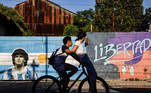 Two persons ride a bike past a graffiti of soccer legend Diego Armando Maradona in Buenos Aires, Argentina, November 27, 2020. REUTERS/Ricardo Moraes TPX IMAGES OF THE DAY