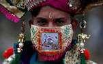"""A participant in traditional costume wearing a mask featuring """"COVID-19 warriors"""" as he attends a rehearsal for Garba, a folk dance, ahead of Navratri, a festival during which devotees worship the Hindu goddess Durga and youths dance in traditional costumes, amidst the coronavirus disease outbreak, in Ahmedabad, India, September 18, 2020. REUTERS/Amit Dave TPX IMAGES OF THE DAY"""