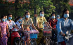 People wearing protective face masks ride bikes on a street, amid the outbreak of the coronavirus disease (COVID-19), in Yangon, Myanmar, December 7, 2020. Picture taken December 7, 2020. REUTERS/Shwe Paw Mya Tin