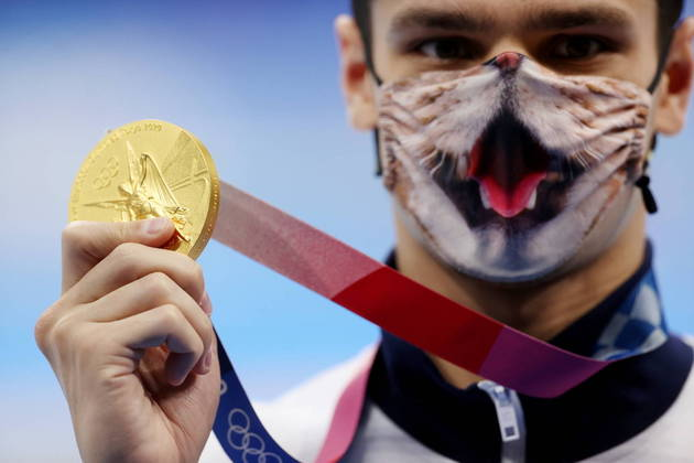 A pandemia da covid-19, ainda em curso no mundo, se reflete nos Jogos Olímpicos de Tóquio 2020. Conscientes da importância da prevenção, os exibem máscaras de proteção facial exóticas nas competições olímpicas. Nessa imagem, o russo Evgeny Rylov mostra a medalha de ouro que conquistou na natação