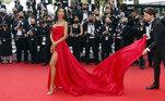 Maylin Aguirre chegou na exibição de France combinando a cauda longa do vestido com tecido leve, deixando um rastro vermelho por onde passava