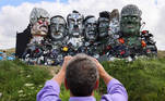 """A man photographs """"Mount Recyclemore"""", an artwork depicting the G7 leaders looking towards Carbis Bay, made from electronic waste by Joe Rush and Alex Wreckage, ahead of the G7 summit, at Hayle Towans in Cornwall, Britain, June 8, 2021. REUTERS/Tom Nicholson REFILE – CORRECTING ARTWORK NAME AND ADDING ARTIST TPX IMAGES OF THE DAY"""