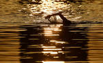 A swimmer trains in the early morning in the Serpentine lake in London, Britain, March 31, 2021. REUTERS/Toby Melville