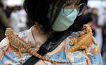 A woman carries two geckos on her shoulders at the Pet Expo Thailand in Bangkok, Thailand, September 6, 2020. REUTERS/Soe Zeya Tun TPX IMAGES OF THE DAY