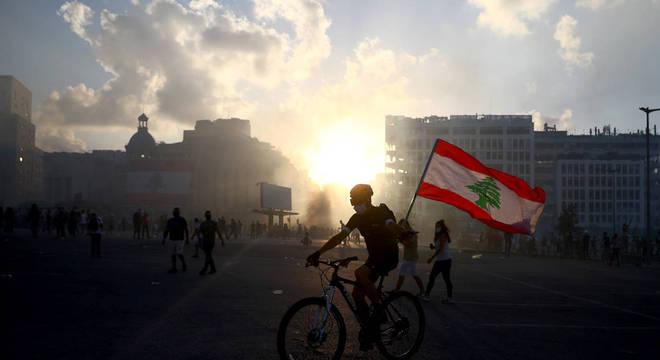 Manifestante com bandeira do Líbano em meio a nuvem de gás lacrimogêneo
