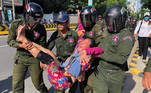 A woman is carried by police officers after security guards broke up a small protest near the Chinese embassy opposing alleged plans to boost Beijing's military presence in the country, in Phnom Penh, Cambodia October 23, 2020. REUTERS/Heng Mengheang NO REALES NO ARCHIVES TPX IMAGES OF THE DAY