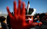 Homem indígena protesta em Brasília. Manifestantes criticam o posicionamento do governo federal em relação às vacinas contra a covid-19