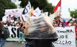No Rio de Janeiro (RJ), manifestantes carregam bandeiras, máscaras e cartazes com mensagens contra o governo e pedindo o impeachment