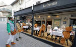"""People look at giant teddy bears sitting on chairs at tables, installed by the restaurant owner to brighten up his empty restaurant """"La Crevette"""" in Saint-Maxime during the national lockdown to combat a resurgence of the coronavirus disease (COVID-19) outbreak in France, December 1, 2020. REUTERS/Eric Gaillard"""