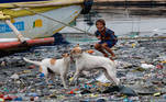 A boy reacts as dogs play along the riverbank of Pasig river, in Manila, Philippines, June 10, 2021. REUTERS/Lisa Marie David