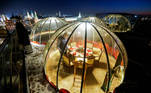 A waiter sets a table inside a transparent pod offered for private Christmas meals with backdrop of the Kremlin and Red Square on the rooftop of Ritz-Carlton hotel in Moscow, Russia December 8, 2020. Picture taken December 8, 2020. REUTERS/Maxim Shemetov TPX IMAGES OF THE DAY