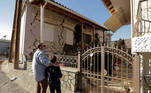 People look at a damaged house following an earthquake in the village of Damasi, in central Greece, March 3, 2021. REUTERS/Thanos Floulis